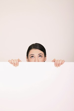 Woman behind blank placard looking up Stock Photo - 8147913