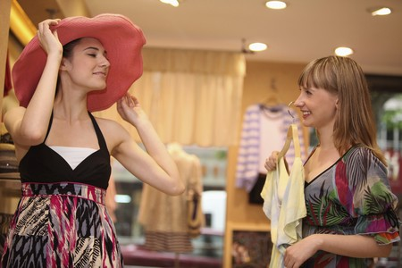 european ethnicity: Woman trying on a hat while her friend is holding up a blouse Stock Photo