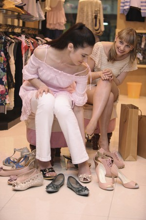 Woman trying on shoes while her friend watches from the side photo