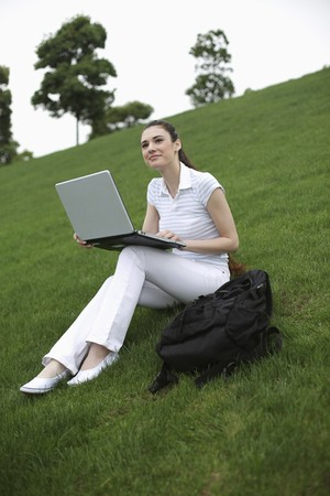Woman using laptop outdoors photo