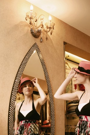 Woman trying on a hat photo