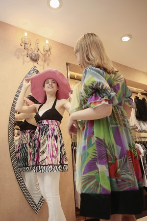 Woman trying on a hat while her friend is holding up a blouse photo