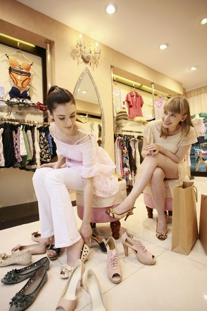 Woman trying on shoes while her friend watches from the side Stock Photo - 8149228