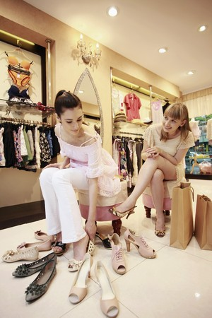Woman trying on shoes while her friend watches from the side Stock Photo - 8149168