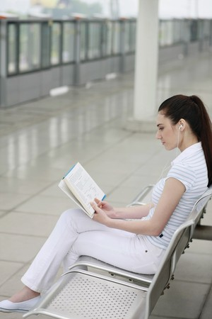 Woman reading book while listening to music photo
