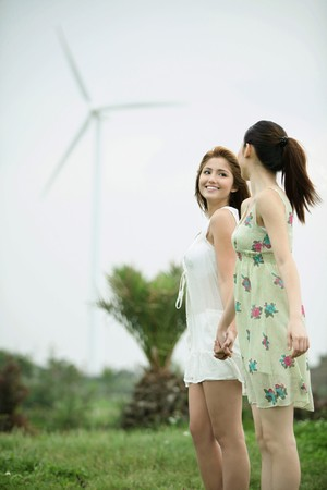 Women holding hand outdoors enjoying the cool wind photo