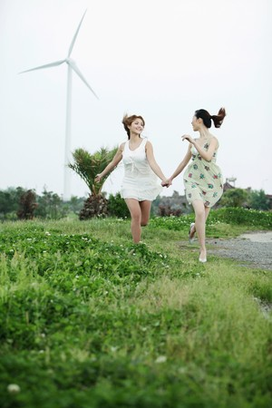 Women holding hands and running together photo
