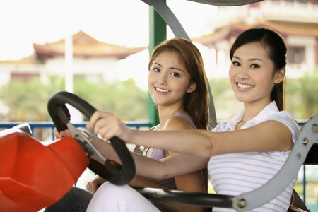Women sitting in carnival ride at amusement park Stock Photo - 8186000