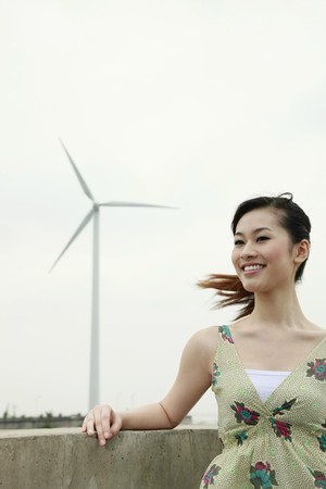 Woman relaxing outdoors with wind mill in the background Stock Photo - 8190031
