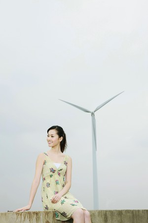 Woman relaxing outdoors with wind mill in the background Stock Photo - 8190059
