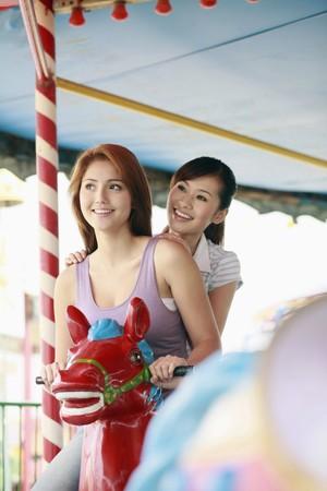 Women riding carousel horses at amusement park photo