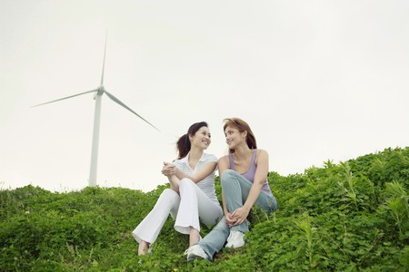 Women relaxing outdoors with wind mill in the background photo