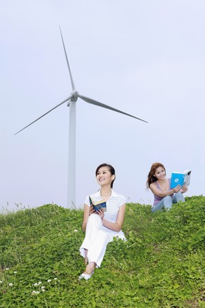 Women reading outdoors with wind mill in the background photo