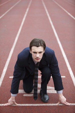 Businessman crouching at starting line of track photo