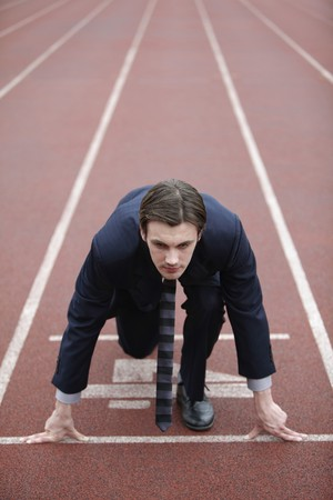 Businessman crouching at starting line of track Stock Photo - 8227702