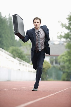 running businessman: Businessman running on track
