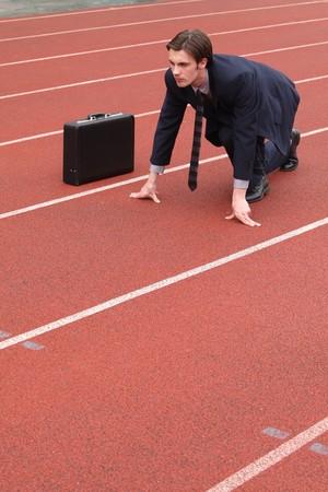 pista de atletismo: Hombre de negocios agacharse en la pista de atletismo Foto de archivo