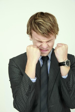 Businessman with eyes closed showing fists photo