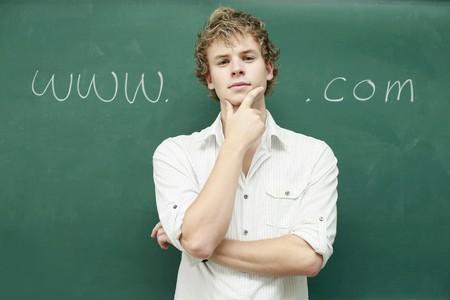 Man standing in front of blackboard with internet link written on it photo