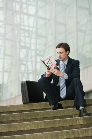 Businessman reading on stairs Stock Photo - 8227750