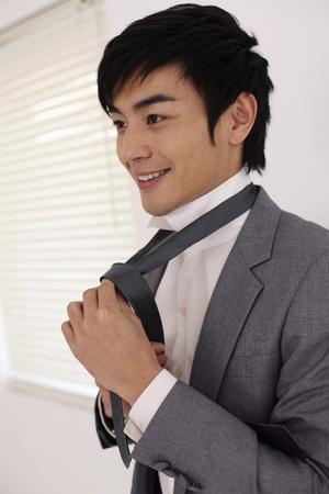 Man tying his tie photo