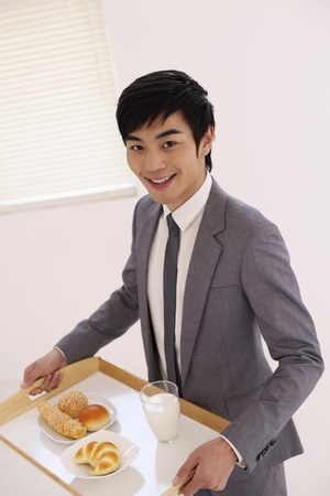 Man carrying breakfast in tray photo