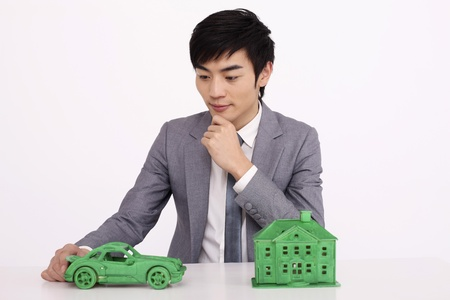 Man contemplating between toy car or green house model photo
