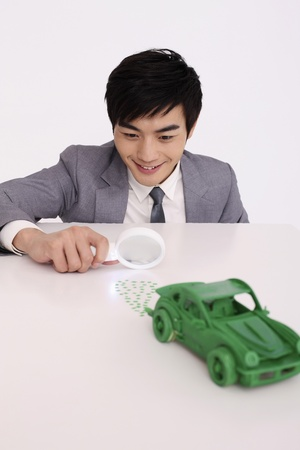 Man using magnifying glass to look at green exhaust waste Stock Photo - 8260311