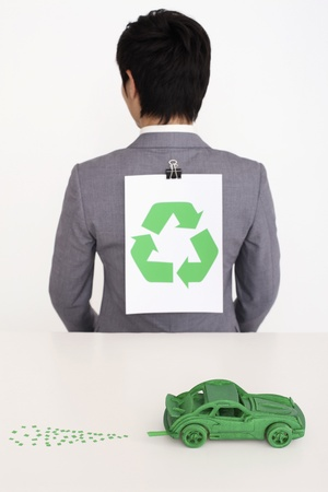 Man with recycling symbol clipped on the back of his suit photo