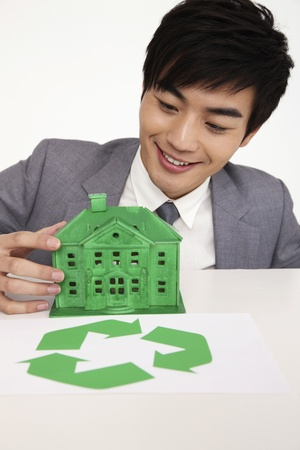Man holding green house model with recyling symbol on the table photo