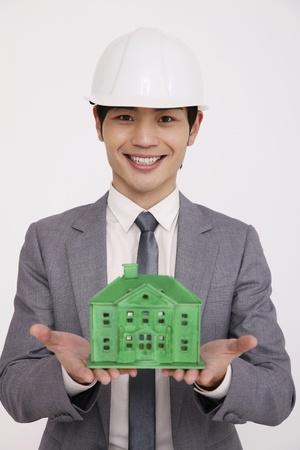 safety helmet: Hombre vistiendo casco de seguridad mantiene el modelo de casa verde  Foto de archivo