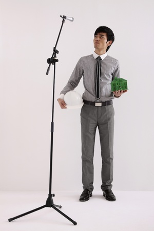 Man holding safety helmet and green house model with microphone stand in front of him photo