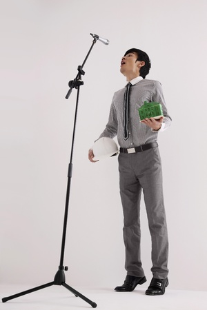 Man on tiptoe trying to reach the microphone
