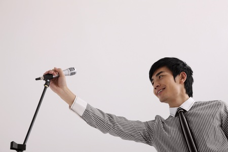 Man holding microphone on stand photo