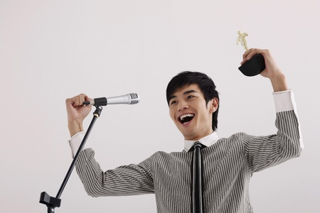 Man cheering into microphone with trophy in hand photo