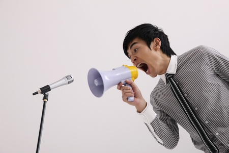 Man shouting into megaphone aiming at the microphone photo