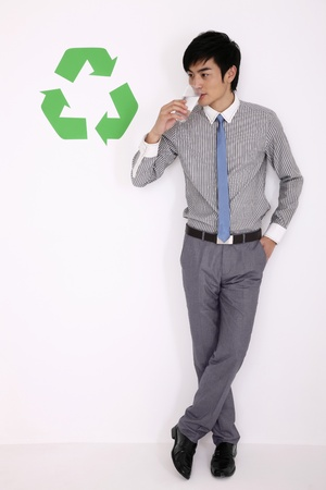 Man drinking a glass of water beside recycling symbol photo