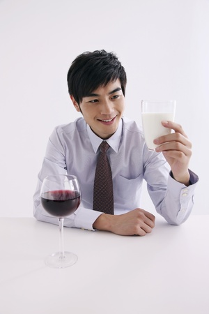Man holding a glass of milk smiling Stock Photo - 8260378