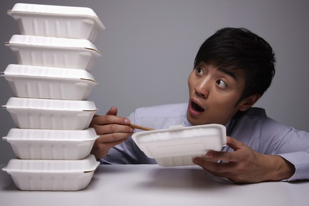 Man looking at stacked take out food photo