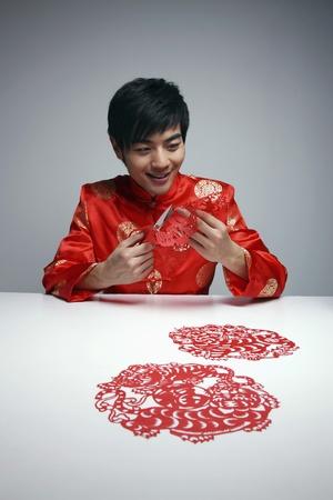 paper cutting: Man making red paper cuttings