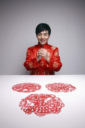 Man with hands clasped wishing Happy Chinese New Year Stock Photo - 8260352