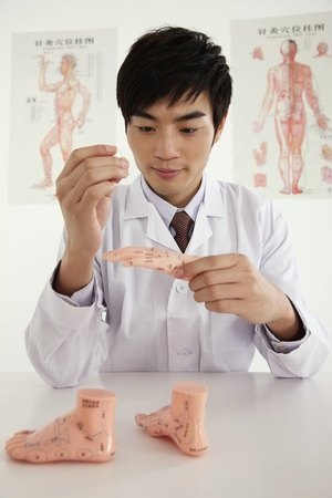Man practising acupuncture on anatomical model photo