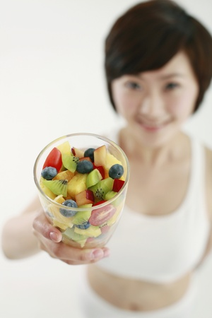 Woman holding a glass of mixed fruits, focus on foreground Stock Photo - 8260165