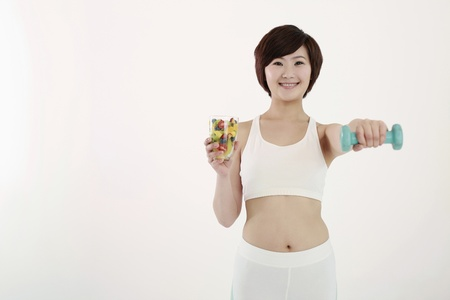 Woman holding a glass of mixed fruits and lifting a dumbbell Stock Photo - 8260020