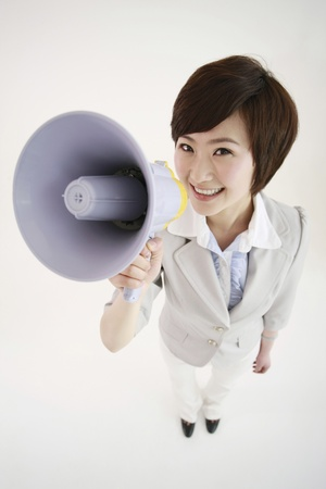 Businesswoman talking into a megaphone Stock Photo - 8260032