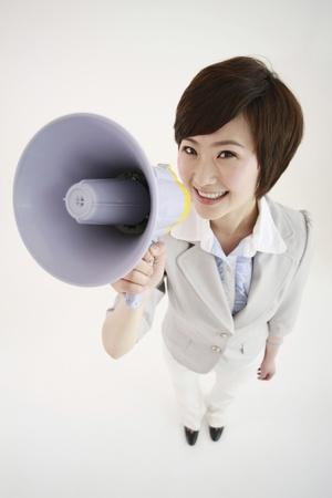 Businesswoman talking into a megaphone Stock Photo - 8260032
