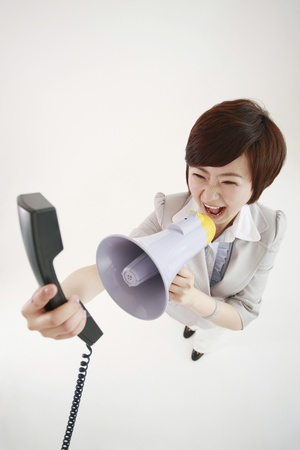 Businesswoman shouting into telephone receiver using a megaphone photo
