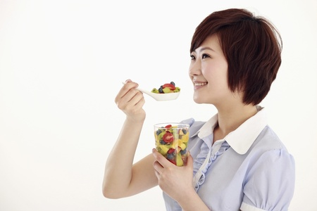 Businesswoman holding a spoonful of mixed fruits photo