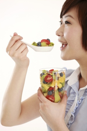 Businesswoman eating a spoonful of mixed fruits photo