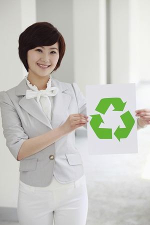 Businesswoman holding a paper with recycling symbol photo